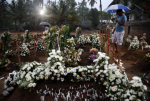 People come to the site of a mass burial to pay their respects to victims of a string of suicide bomb attacks on churches and luxury hotels on Easter Sunday, in Negombo, Sri Lanka. Photo by Athit Perawongmetha/Reuters