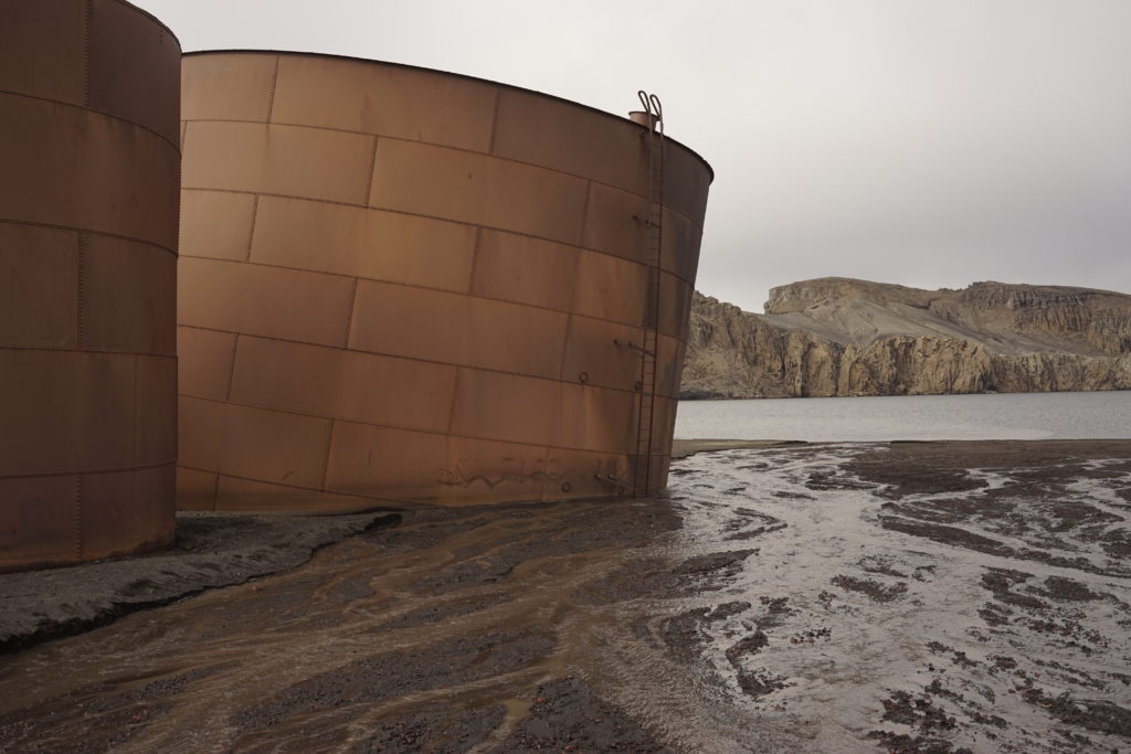 Rusting whale oil tanks are some of the only remnants of the Deception Island whaling operation. Image by William Brangham