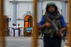 Priests are seen in the background as a security personnel stands guard in front of St Anthony's Shrine, days after a string of suicide bomb attacks across the island on Easter Sunday, in Colombo, Sri Lanka. Photo by Danish Siddiqui/Reuters