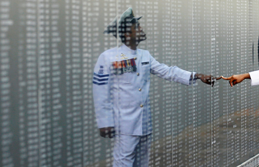 A Navy officer looks at the heroes' name board of a war memorial, d…