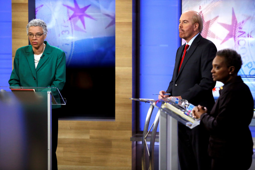 Fox 32 Chicago moderator Mike Flannery (center) and Chicago mayoral election candidates Toni Preckwinkle (left) and Lori L...