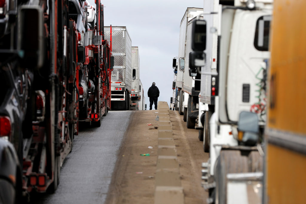 A man stands between trucks waiting in a long queue at border customs control to cross into the U.S, caused by the redeployment of border officers to deal with a surge in migrants, at the Otay border crossing in Tijuana, Mexico, April 3, 2019. Photo by Carlos Jasso/Reuters