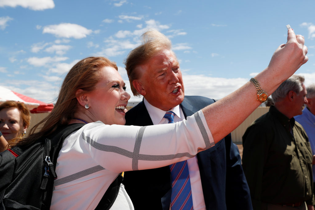U.S. President Donald Trump stops to pose for a selfie as he visits the U.S.-Mexico border wall in Calexico, California, U.S., April 5, 2019. Photo by Kevin Lamarque/Reuters