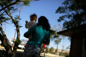 Honduran migrant Karen Lizeth Licona, who is waiting for her court hearing for asylum seekers that returned to Mexico to await their legal proceedings under a new policy established by the U.S. government, carries a child at a fire station used as a temporary shelter, in Ciudad Juarez, Mexico, April 7, 2019. Photo by Jose Luis Gonzalez/Reuters