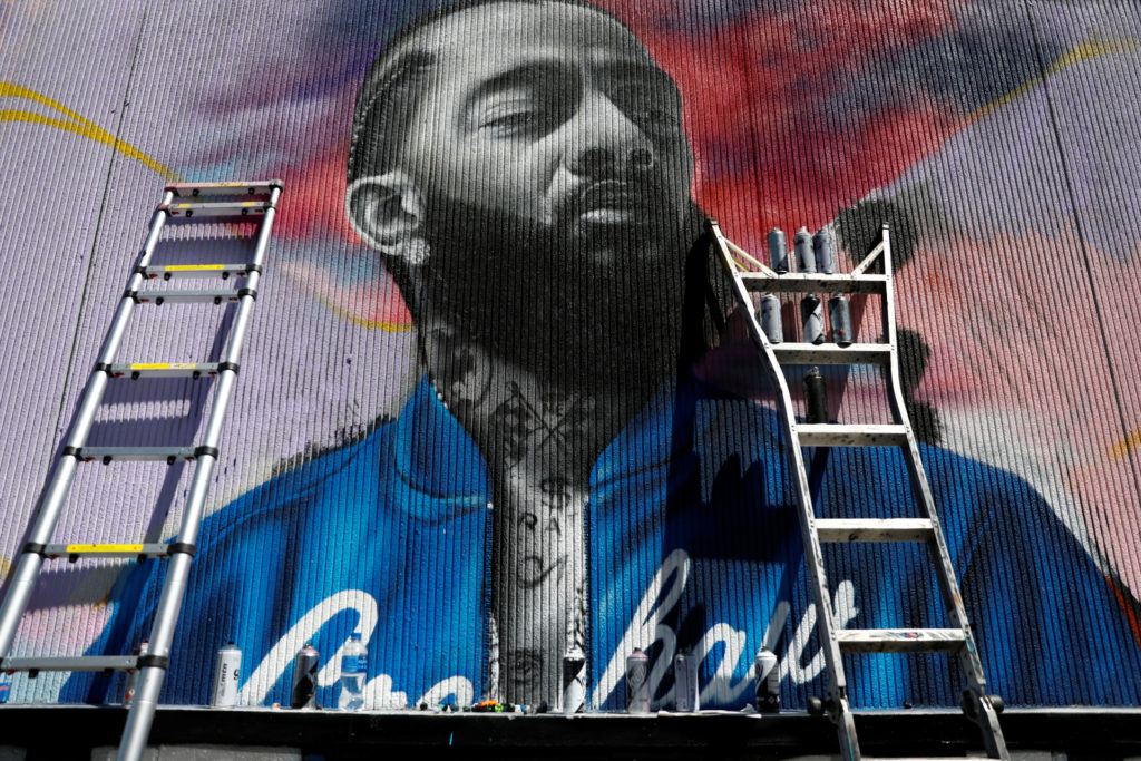 A mural is pictured as people mourn the shooting death of musician Nipsey Hussle outside of his The Marathon Clothing store on Slauson Avenue in Los Angeles, California on April 7, 2019. Photo by Patrick T. Fallon/Reuters