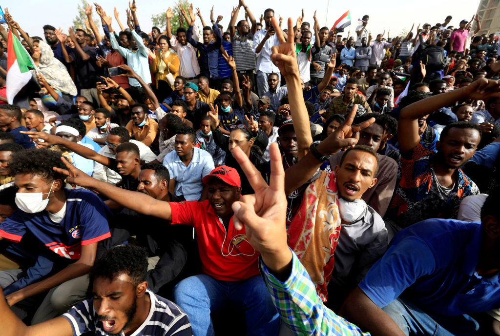 Sudanese demonstrators cheer as they attend a protest rally demanding Sudanese President Omar Al-Bashir to step down outside the Defence Ministry in Khartoum, Sudan, April 11, 2019. Photo by Reuters