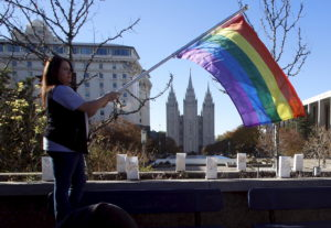 Sandy Newcomb stands with a flag near the Salt Lake Temple after members of The Church of Jesus Christ of Latter-day Saints mailed their membership resignation to the church in Salt Lake City, Utah in November 2015. The resignations were prompted by the Mormon church policy barring the children of married same-sex couples from receiving baptism. Photo byJim Urquhart/Reuters