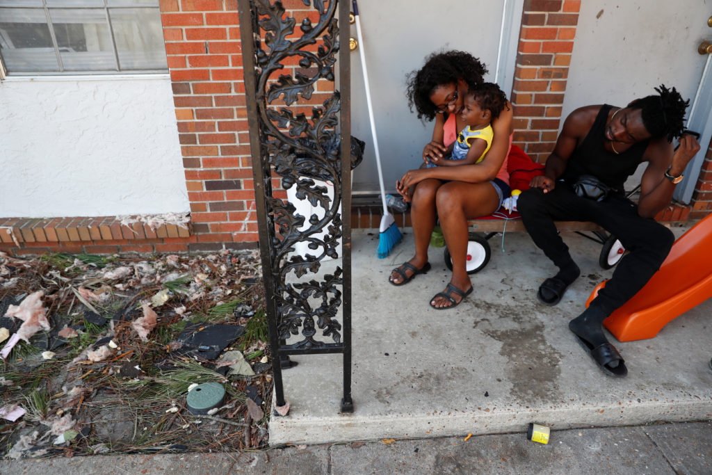 Shauntese Russell, 23, and Maurice Brown, 24, sit with their son, Maurice Jr., amid debris left by Hurricane Michael outside their apartment in Lynn Haven, Florida, on October 14, 2018. Renters are often at a significant disadvantage after a storm because recovery efforts are focused on repairing property, research shows. Photo by Terray Sylvester/Reuters