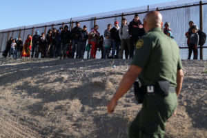 A group of Central American migrants surrenders to U.S. Border Patrol Agent Jose Martinez south of the U.S.-Mexico border fence in El Paso, Texas, March 6, 2019. The Department of Homeland Security has reassigned hundreds of agents away from ports of entry to handle immigrants coming across the border. Photo by Lucy Nicholson/Reuters