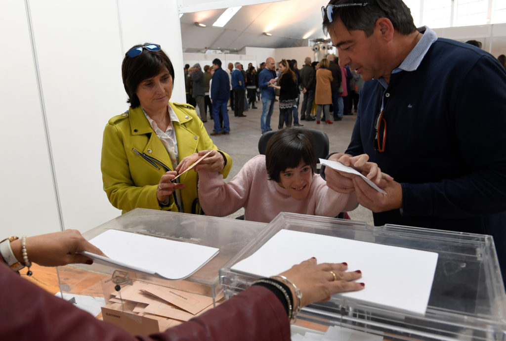 Laura Sanchez Herrero is helped by relatives to exercise her right to vote, during Spain's general election, in Pola de Siero, April 28, 2019. For the first time in Spain people with intellectual disabilities have the right to vote. Photo by Eloy Alonso/Reuters