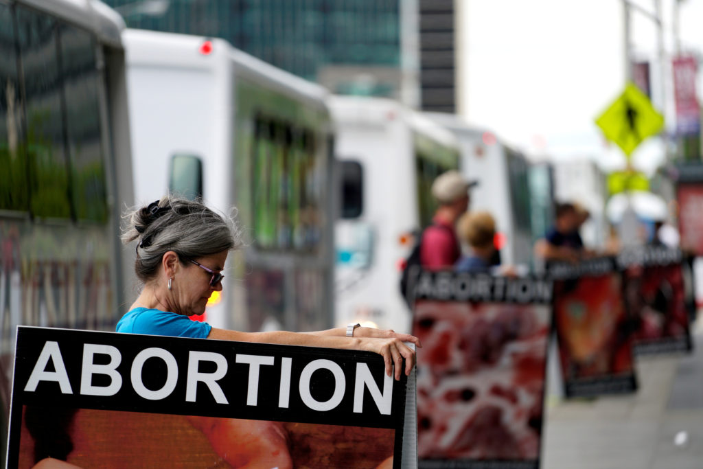 Anti-abortion protestors holding what they said were photos of abortions stand outside the building where new organizations are working at the Republican Presidential Convention in Cleveland July 14, 2016. Photo by REUTERS/Rick Wilking