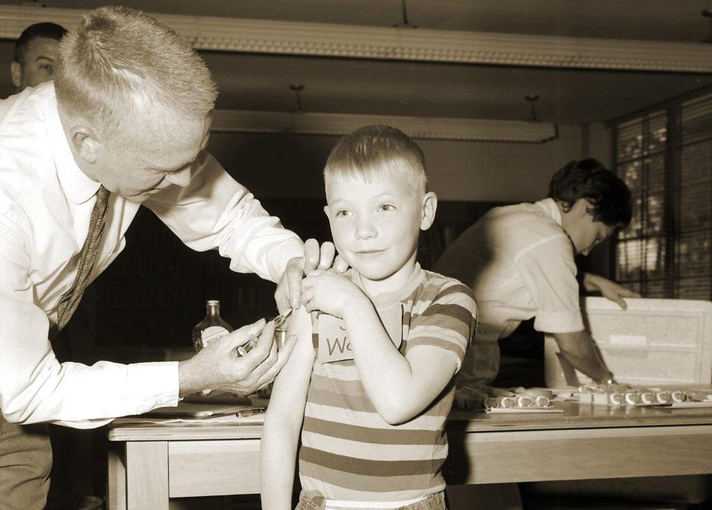 An unidentified boy receives an early version of a measles vaccination at the Fernbank School in Atlanta, Georgia, 1962. Photo by the CDC