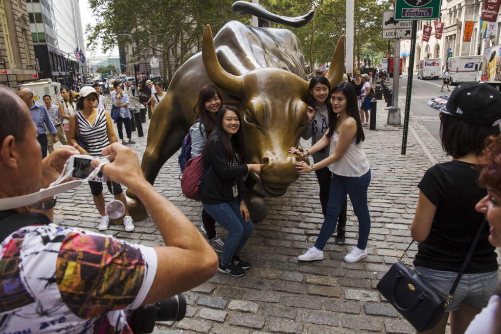 Chinese tourists pose for photographs with a landmark statue of a bull in New York August 24, 2015. Photo by Lucas Jackson...