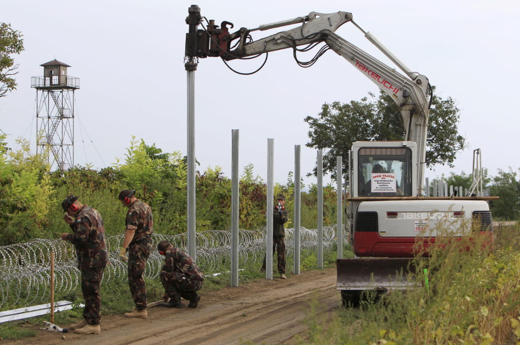 Hungarian army soldiers erect a fence on the border with Croatia near Sarok, Hungary, September 20, 2015. Built in a matter of weeks by soldiers, prison labourers and cadres of the unemployed, a vast new wall along Balkan frontiers was a monument to the ruthless efficiency with which Prime Minister Viktor Orban has mobilized Hungary against migrants. Photo by Bernadett Szabo/Reuters