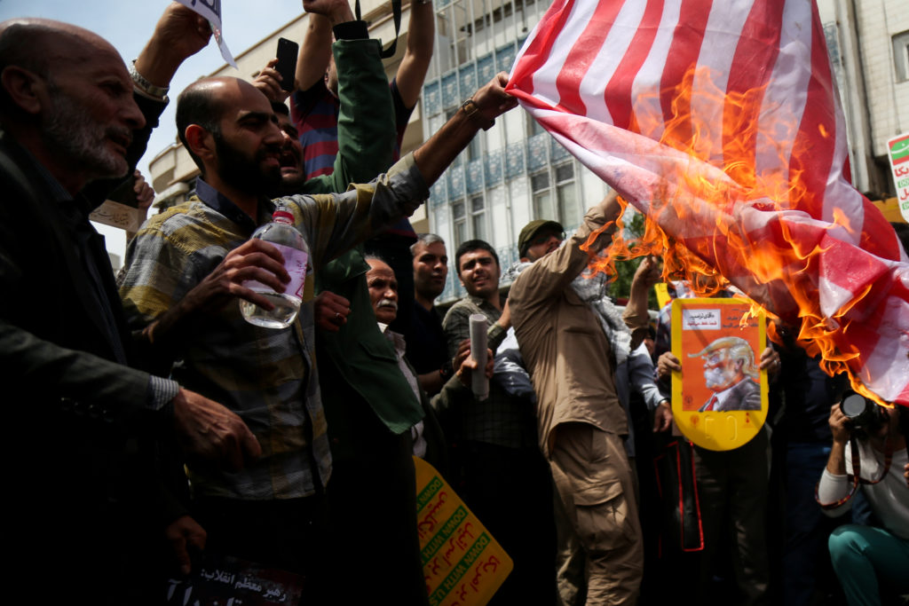 FILE PHOTO: Iranians burn a U.S. flag during a protest against President Donald Trump's decision to walk out of a 2015 nuc...