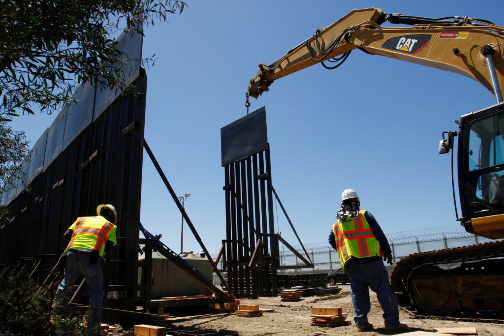 Construction workers are seen next to heavy machinery while replacing a section of the old Mexico-U.S. border as seen from Tijuana, Mexico, on June 28, 2018. Photo by Jorge Dunes/Reuters