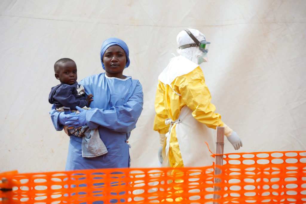 Mwamini Kahindo, an Ebola survivor working as a caregiver to babies who are confirmed Ebola cases, holds an infant outside the red zone at the Ebola treatment centre in Butembo, Democratic Republic of Congo, on March 25, 2019. Photo by Baz Ratner/Reuters