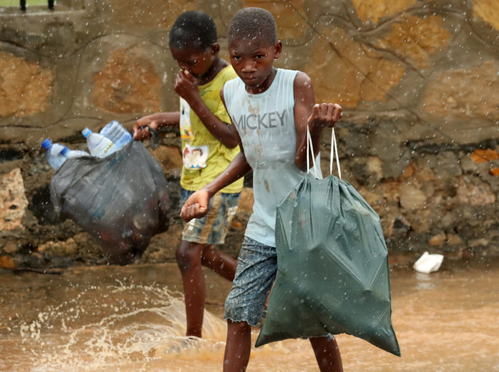 Children walk through flooded streets as rain falls in the aftermath of Cyclone Kenneth in Pemba, Mozambique, on April 30,...