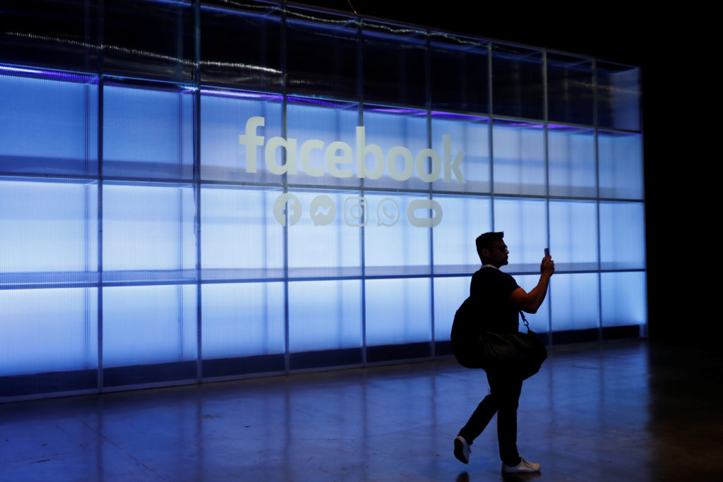 An attendee takes a photograph of a sign during Facebook Inc's F8 developers conference in San Jose, California, on April ...