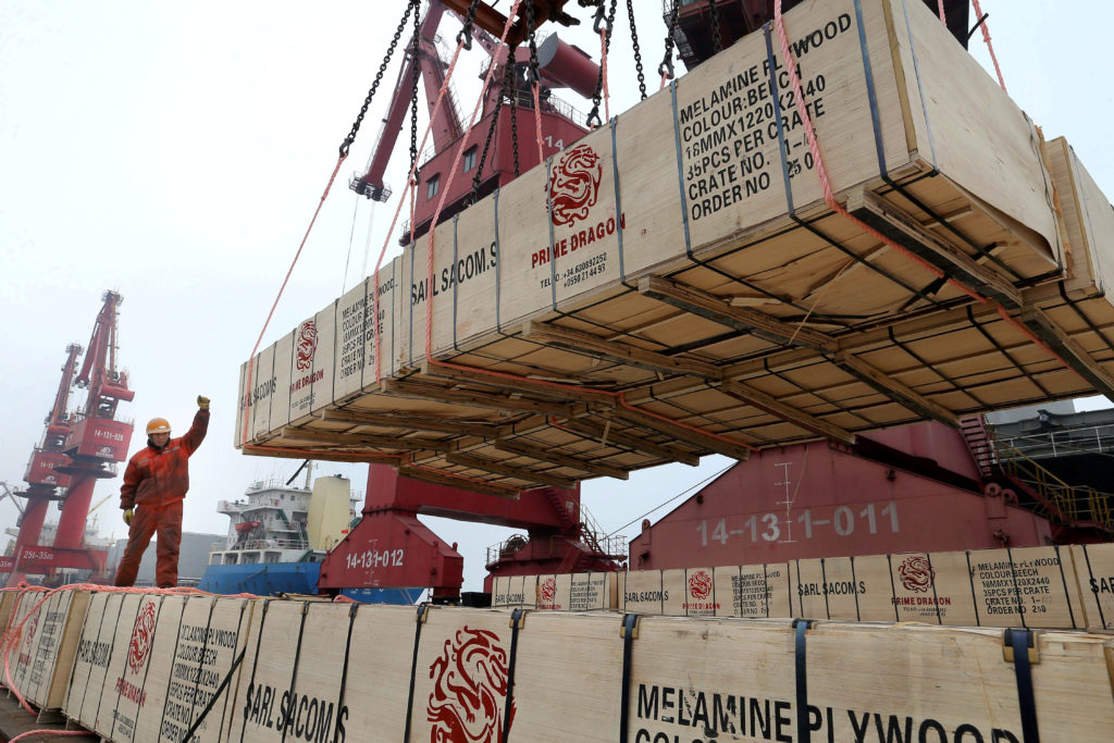 A worker gestures as a crane lifts goods for export onto a cargo vessel at a port in Lianyungang, Jiangsu province, China ...