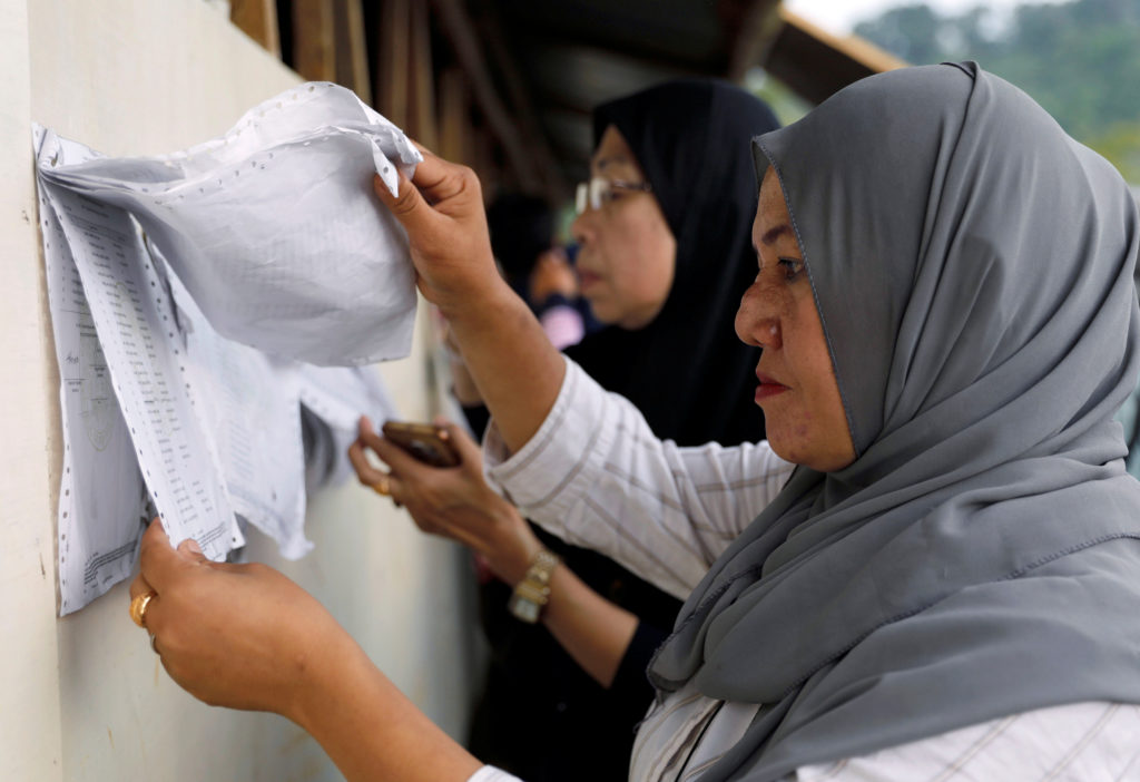 Voters look for their names from a list outside makeshift polling precints in Marawi City, Lanao Del Sur province, Philipp...