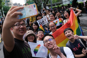 Same-sex marriage supporters pose for group photo after Taiwan became the first place in Asia to legalize same-sex marriage, outside the Legislative Yuan in Taipei, Taiwan. Photo by Tyrone Siu/Reuters