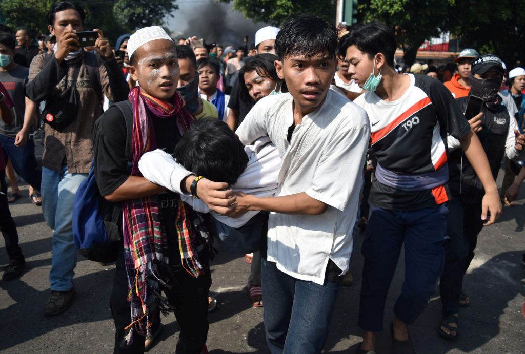 People carry an injured protester to safety during clashes with police in Jakarta, Indonesia, May 22, 2019. Photo by Antara Foto/Aditya Pradana Putra/ via Reuters
