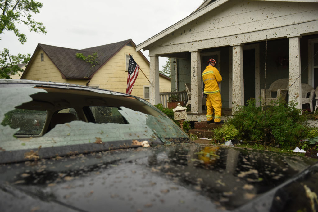 A member of the Jefferson City Fire Department checks houses for people on Woodland Avenue following a tornado touchdown overnight in Jefferson City, Missouri. Photo by Antranik Tavitian/Reuters