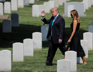 "President Donald Trump walks with first lady Melania Trump among headstones as they take part in the annual ""Flags-In"" event at Arlington National Cemetery ahead of the Memorial Day holiday weekend in Arlington, Virginia. Photo by Carlos Barria/Reuters"