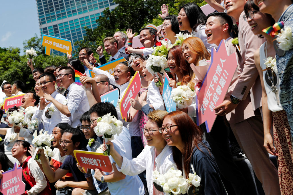 Gay and lesbian newlyweds pose for group photo at a pro same-sex marriage party after registering their marriages in Taipei, Taiwan. Photo by Tyrone Siu/Reuters