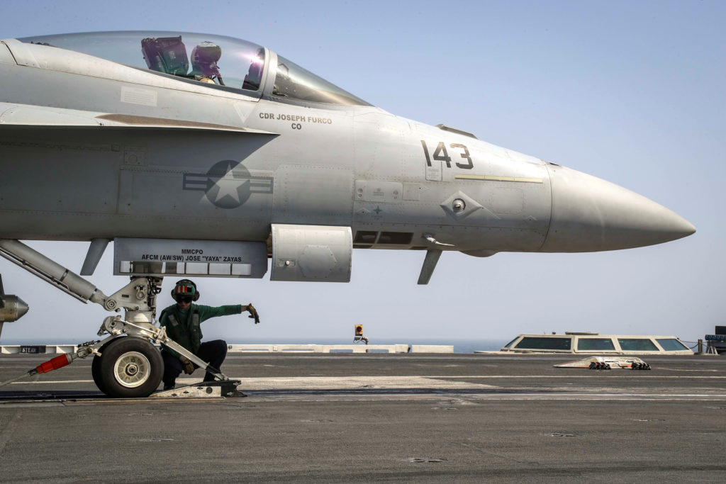 A flight deck crew ensures an F/A-18E Super Hornet is seated in the catapult shuttle on the flight deck of the aircraft ca...