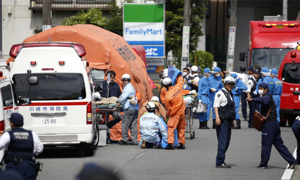 Rescue workers and police officers operate at the site where sixteen people were injured in a suspected stabbing by a man,...