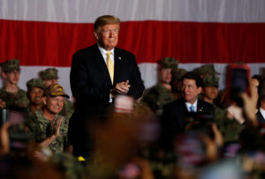 President Donald Trump reacts next to military personnel aboard the USS Wasp as he participates in a Memorial Day Address in Yokosuka, south of Tokyo, Japan on May 28, 2019. Photo by Issei Kato/Reuters
