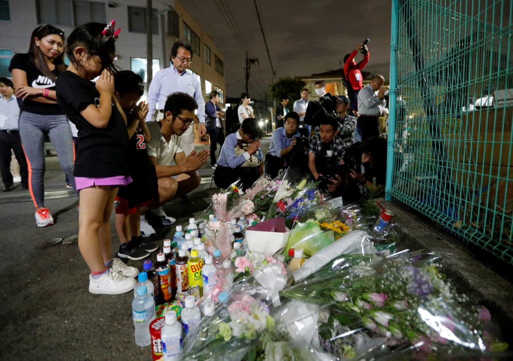 Local residents pray to mourn victims at the site where a stabbing occured in Kawasaki, Japan, May 28, 2019.  Photo by Issei Kato/Reuters