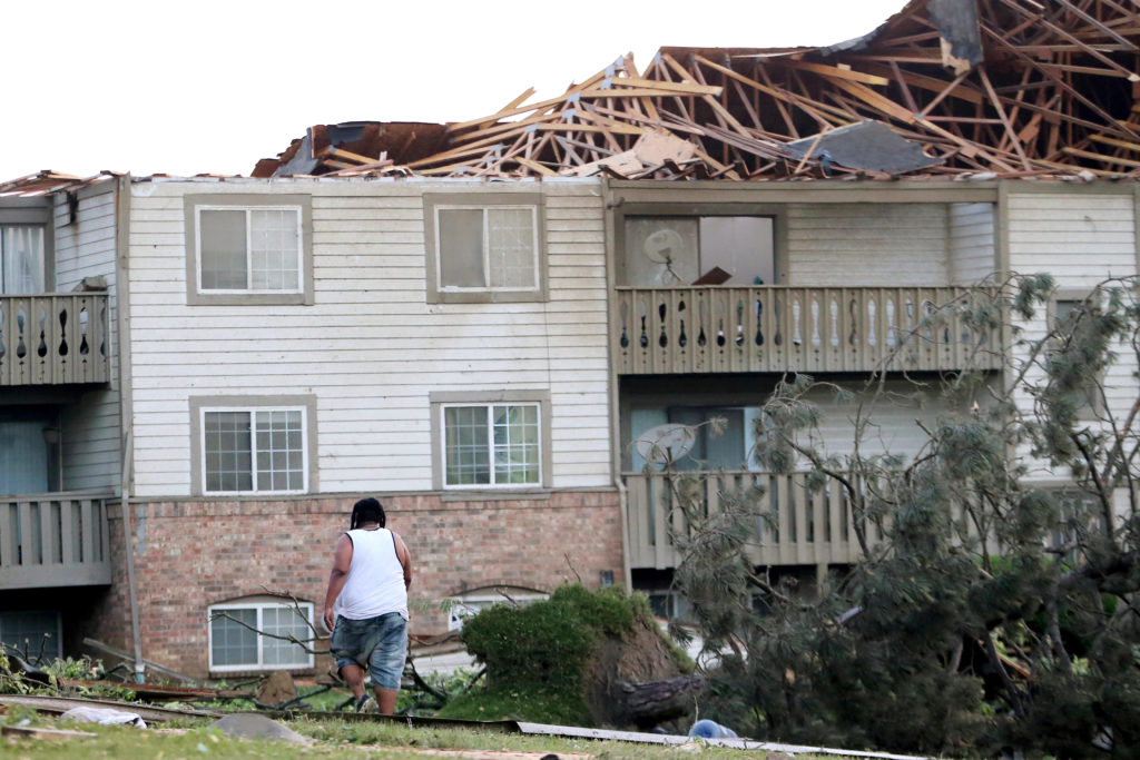 A man walks through the scattered debri outside his apartment building in the morning after a tornado touched down overnig...