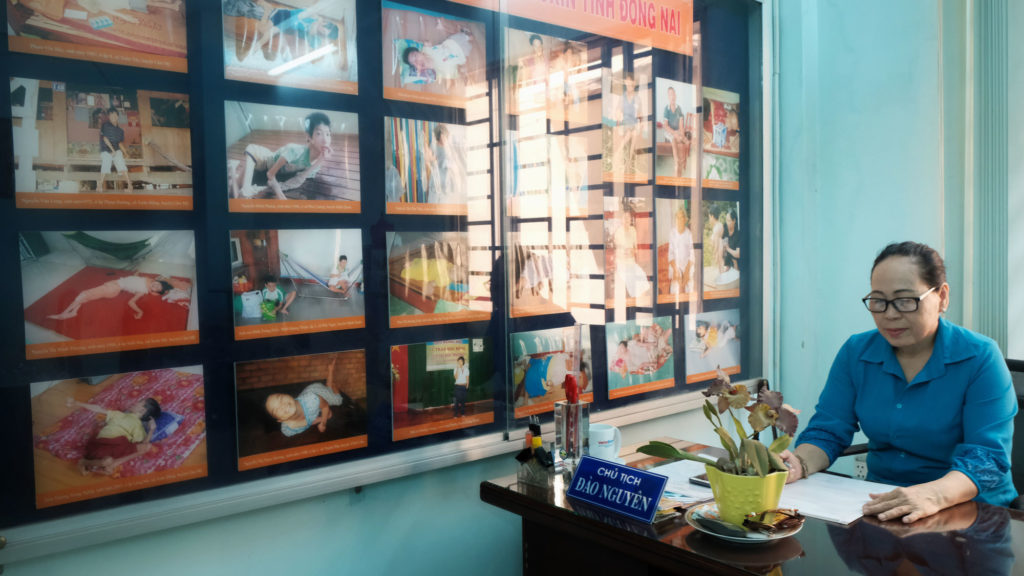 Nguyen Dao, of the Vietnamese Association of Victims of Agent Orange/Dioxin, sits next to photos of some of the more than 1,000 people with dioxin-related disabilities in Bien Hoa. Photo by Cuong Tran/FERN