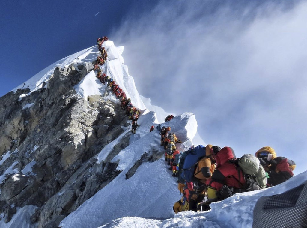 In this photo made on May 22, 2019, a long queue of mountain climbers line a path on Mount Everest. About half a dozen cli...