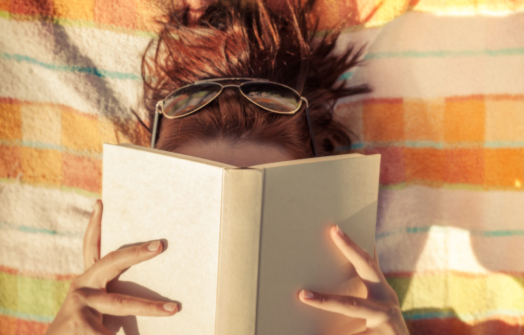 Woman reading book on beach blanket