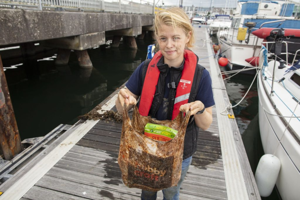 Imogen Napper, the study's lead author, demonstrates that even after years underwater, bags billed as biodegradable can still hold a load of groceries. Image courtesy of the University of Plymouth
