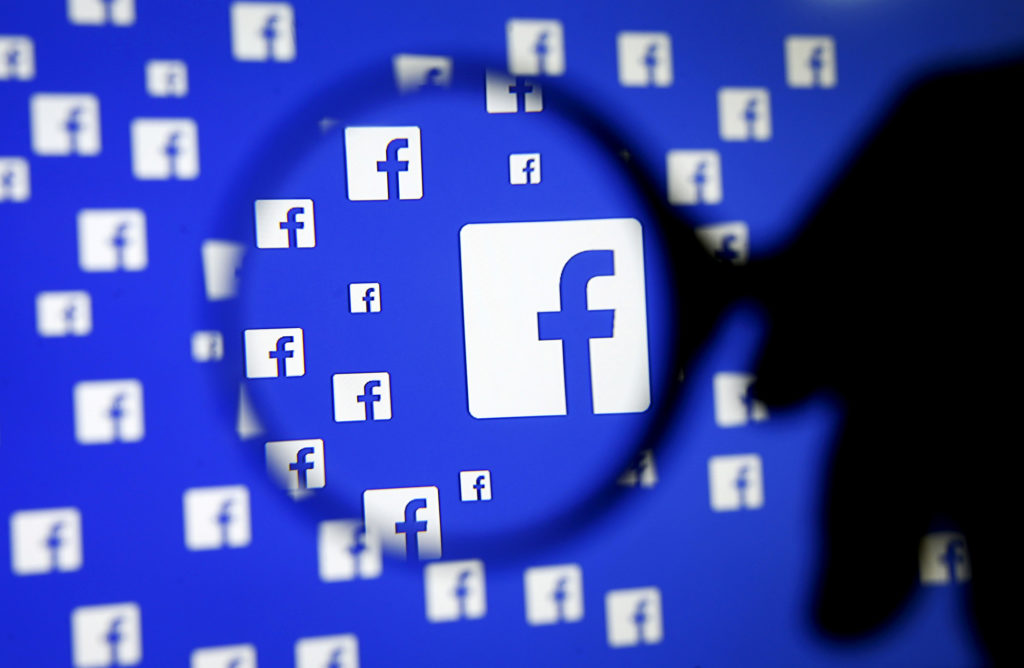 A man poses with a magnifier in front of a Facebook logo on display…