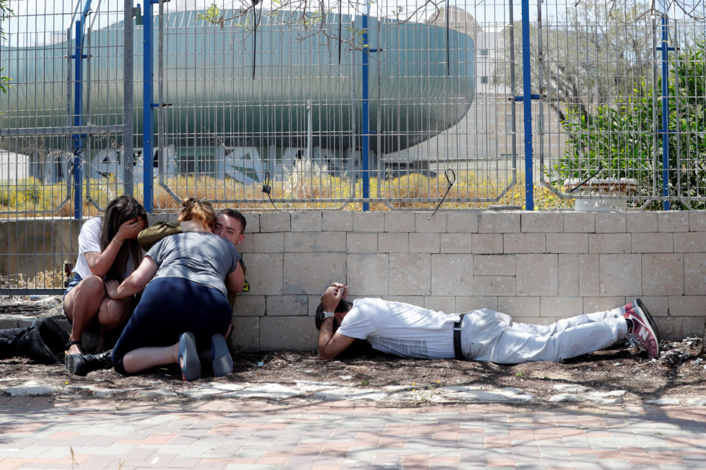 Israelis take cover as they hear sirens warning of incoming rockets from Gaza, during cross-border hostilities, in the southern Israeli city of Ashkelon May 5, 2019. Photo by Ronen Zvulun/Reuters