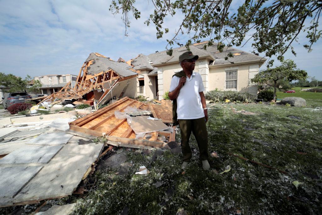 Daniel Williams, of Clayton, Ohio walks through his damaged property after a tornado touched down overnight near Dayton, O...