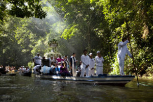 FILE PHOTO: Roman Catholic pilgrims travel in a boat as they accompany the statue of Our Lady of Conception during an annual river procession and pilgrimage along the Caraparu River in Santa Izabel do Para, in the Amazon jungle December 8, 2012. The statue is transported by boat along this small Amazon tributary to a small chapel in the village of Cacoal, where a mass is held. Picture taken December 8, 2012. Photo by Paulo Santos/Reuters