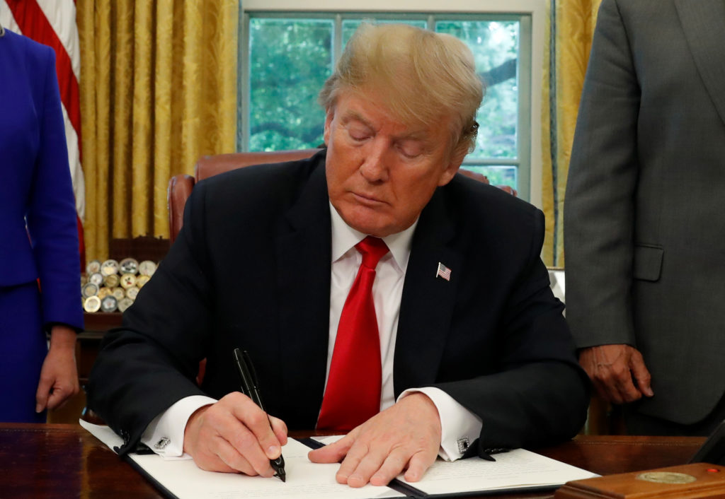 President Donald Trump signs an executive order on immigration policy in the Oval Office of the White House in Washington, June 20, 2018. Photo by Leah Millis/Reuters