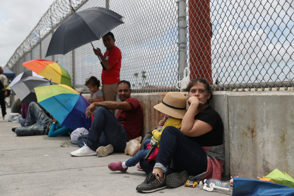 A Honduran mother and her 3-year-old daughter wait with fellow asylum seekers on the Mexican side of the Brownsville-Matamoros International Bridge after being denied entry by U.S. Customs and Border Protection officers near Brownsville, Texas, on June 24, 2018.  Photo by Loren Elliott/Reuters