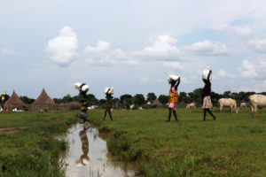 Internally displaced women carry relief food from a distribution by the World Food Programme in the Sudd Swamp near the town of Nyal, in South Sudan August 19, 2018. Picture taken August 19, 2018. Photo by Andreea Campeanu/Reuters