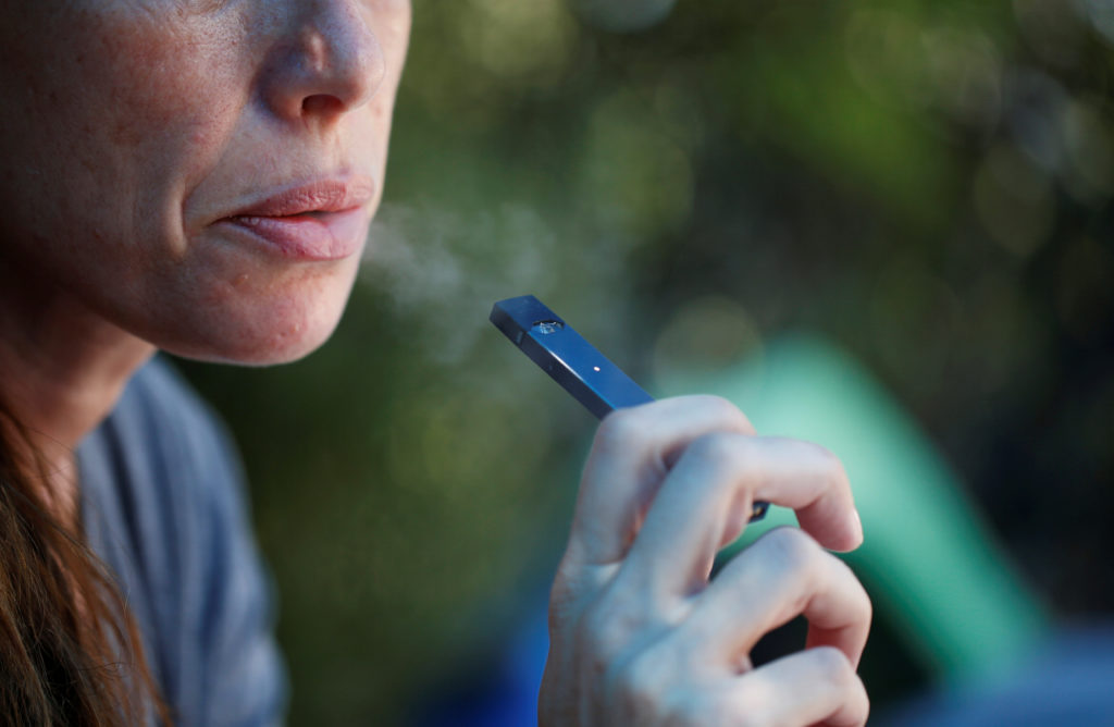 A woman smokes a Juul e-cigarette in this posed picture. Photo by Ronen Zvulun/Reuters
