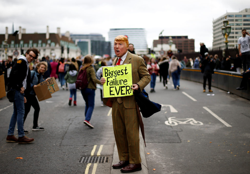 A demonstrator, wearing a mask depicting U.S. President Donald Trump, takes part in a protest against climate change, organized by the YouthStrike4Climate movement, in London, Britain March 15, 2019.  Photo by Henry Nicholls