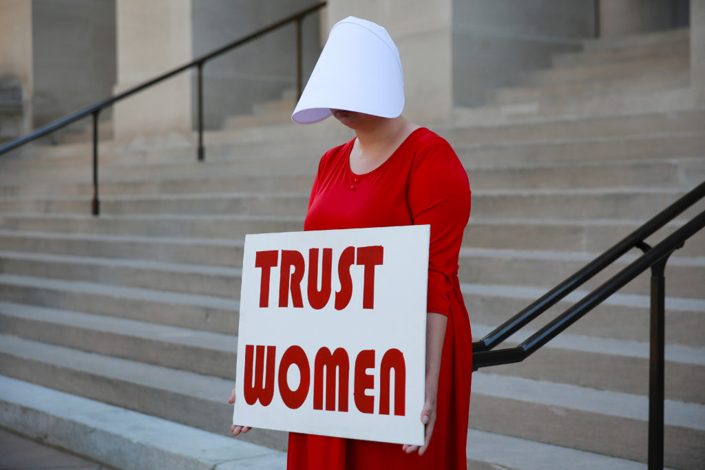 "A woman dressed as a Handmaid holds a sign reading 'Trust Women' in protest of Georgia's anti-abortion ""heartbeat"" bill at the Georgia State Capitol in Atlanta, Georgia, May 7, 2019. The abortion bills have sparked a backlash from abortion rights advocates, but many Americans hold nuanced views on the issue. Photo by Elijah Nouvelage/Reuters"