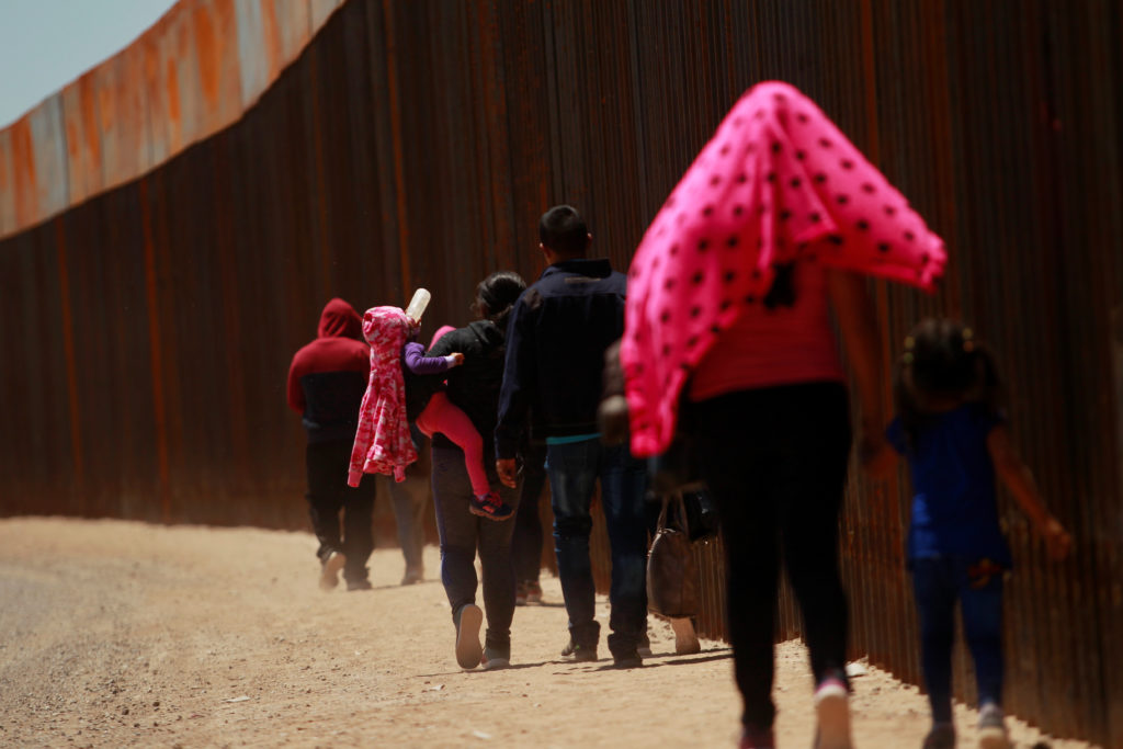 A child drinks a bottle with milk while carried by a woman together with a group of Central American migrants walking next to the U.S.-Mexico border fence after they crossed the borderline in El Paso, Texas, on May 15, 2019. Photo by Jose Luis Gonzalez/Reuters